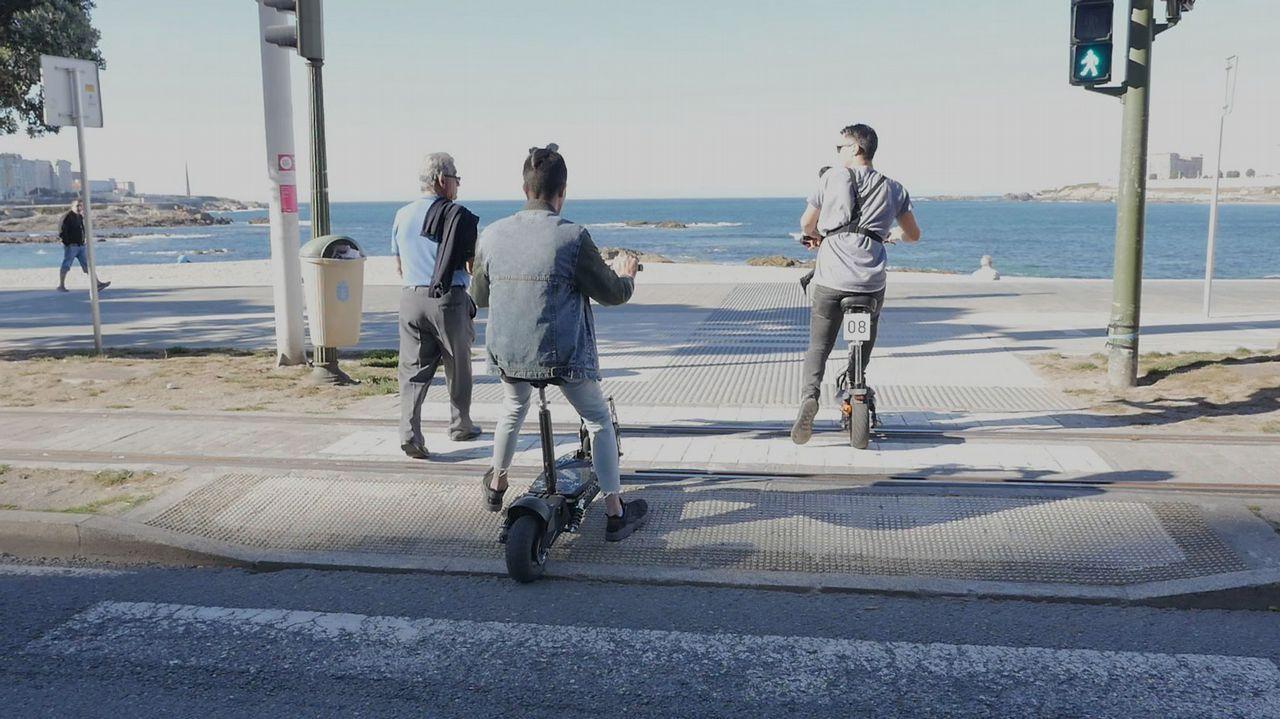 Dos patinetes cruzan un paso de peatones en el paseo marítimo de A Coruña