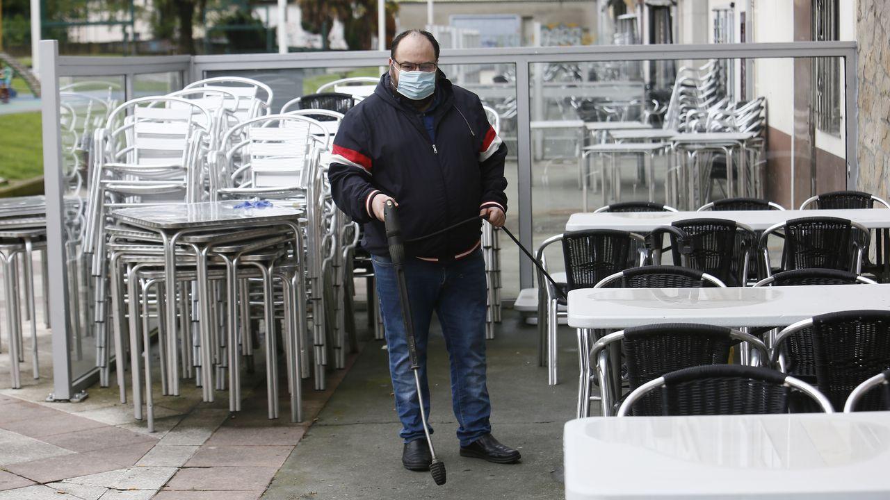 Abilio Golpe, limpiando la terraza de la Vinoteca Aquitania, que reabrirá este martes en el Parquemar de Covas