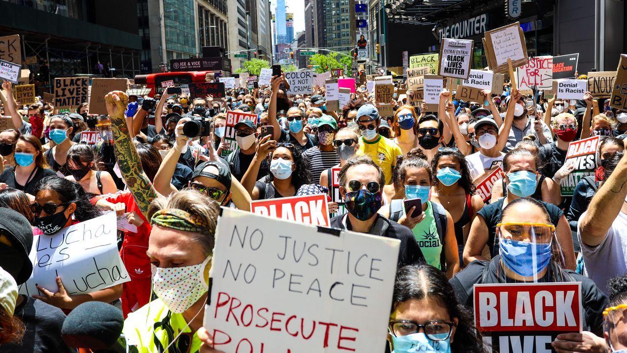 Ciudadanos de Nueva York, ataviados con mascarillas, protestan ayer por la muerte de Floyd