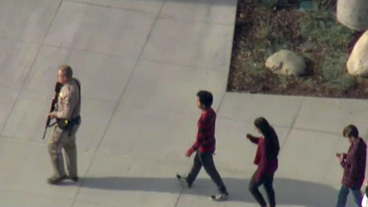 Un policia evacúa a los estudiantes del instituto de Sana Clarita