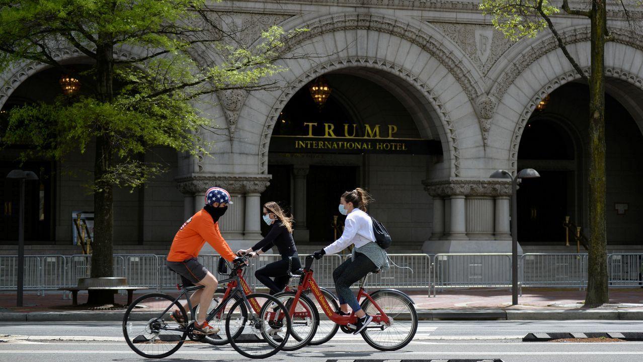 Las mascarillas se convierten en el nuevo complemento universal.Unos ciclistas pasan por delante de la entrada del hotel Trump en Washington