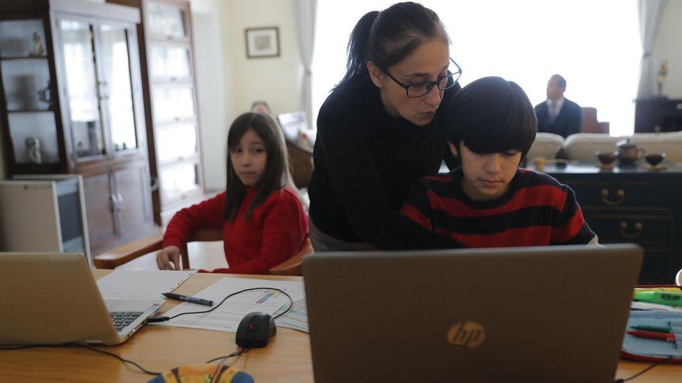 Simón Toledo, en primer término, y su hermana Belén, de 12 y 10 años, reciben lecciones de su madre, la chilena Begoña Soto. Su padre, también chileno y diplomático en Pekín, está al fondo de la sala