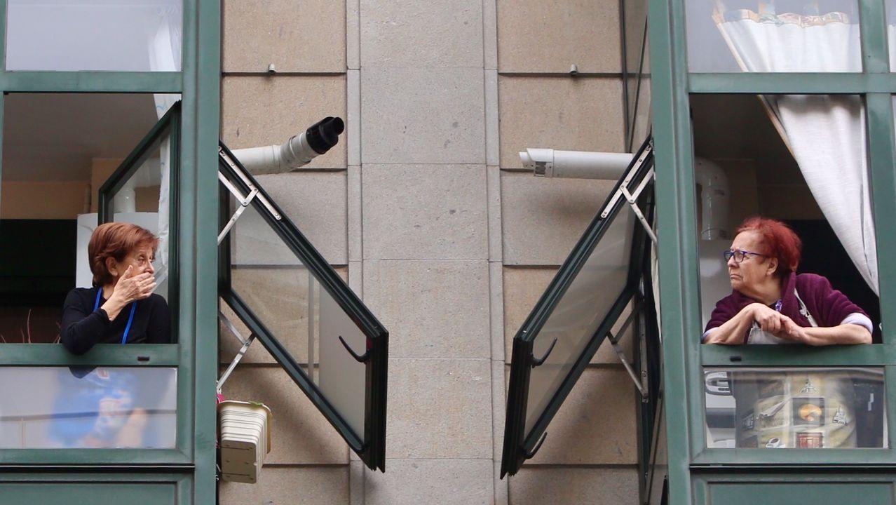 Dos vecinas charlan desde las ventanas de su edificio en el centro de Vigo