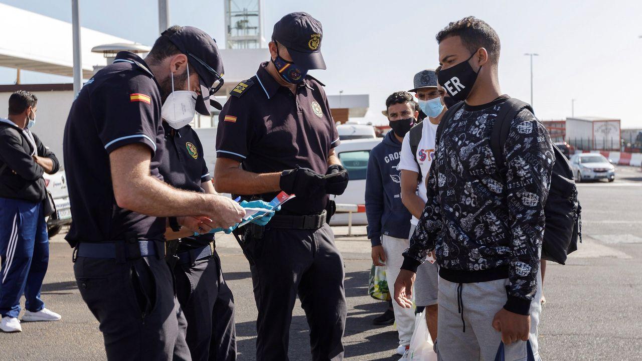 Unos policías revisan los papeles de unos inmigrantes trasladados desde Gran Canaria a Tenerife para ser alojados en un hotel del sur de la isla gracias a la gestion de la Cruz Roja