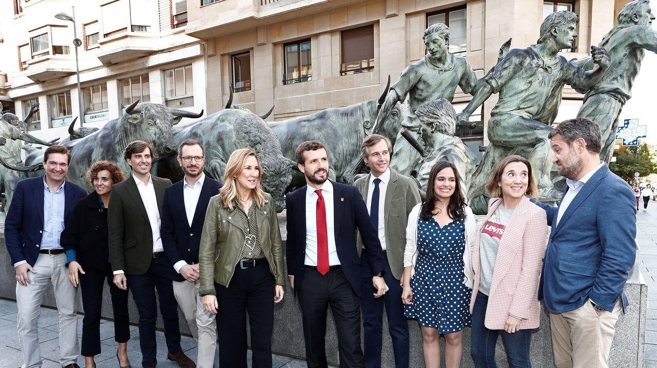 Los presidentes del PP y del PPN, Pablo Casado y Ana Beltrán, junto con el resto de miembros del comité de dirección del partido, posan junto al monumento al encierro en Pamplona