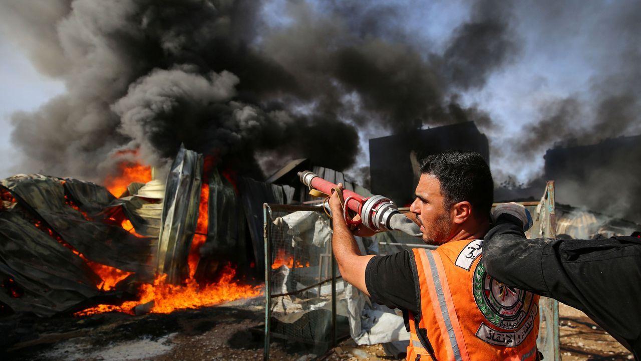Un bombero palestino intenta sofocr el incendio en una fábrica en la que impacto un misil israelí