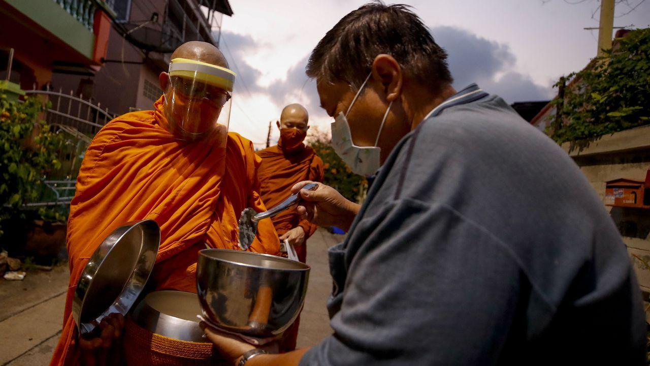 Los monjes budistas tailandeses, con pantallas protectoras, reciben comida durante la limosna matutina en Samut Prakan