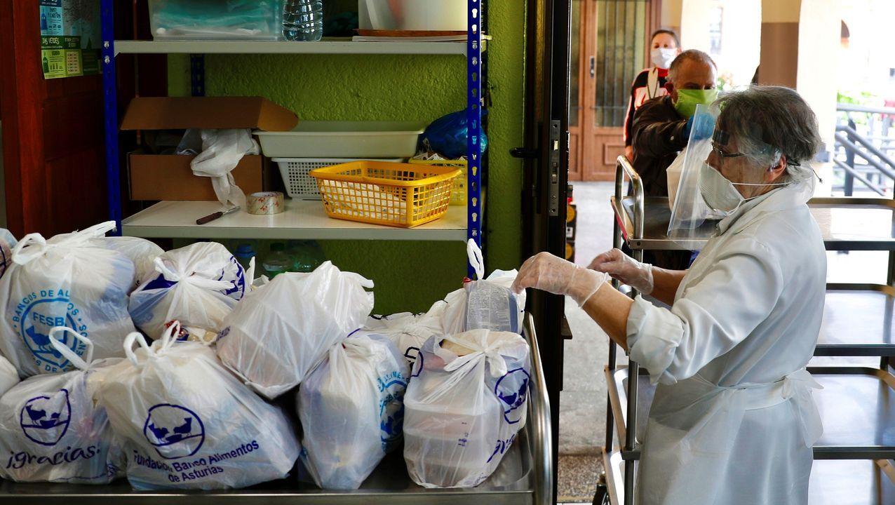 Voluntarios de la Cocina Económica de Oviedo preparan bolsas con el menú de comida y cena para entregar a las familias más necesitadas que acuden a esta entidad
