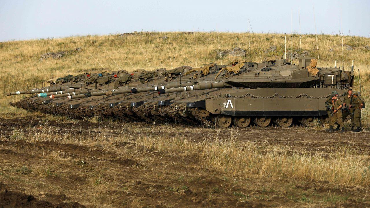 Soldados israelíes se paran junto a los tanques Merkava Mark IV en un área de despliegue de los altos del Golán, área siria que ocupa militarmente