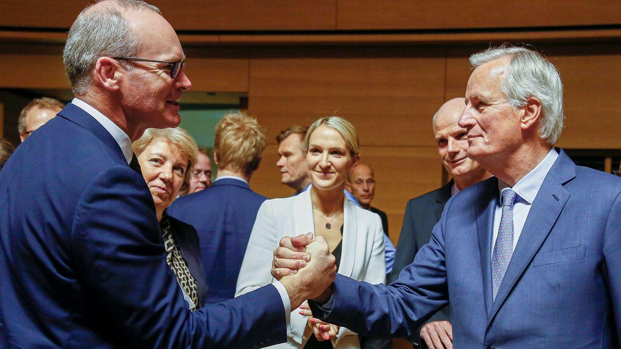 El ministro irlandés, Simon Coveney, saluda a Barnier a la llegada al Consejo de Exteriores