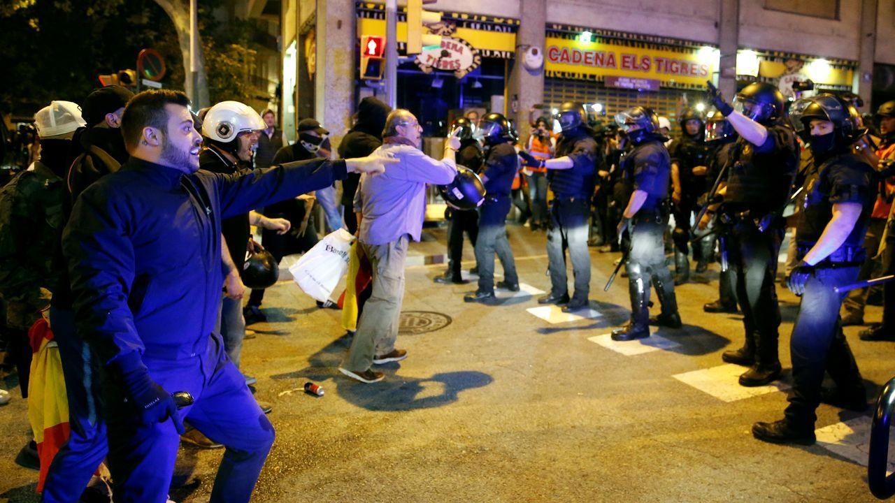 Un grupo de manifestantes con banderas españolas se encaran contra agentes antidisturbios, durante una de las concentraciones convocadas este jueves