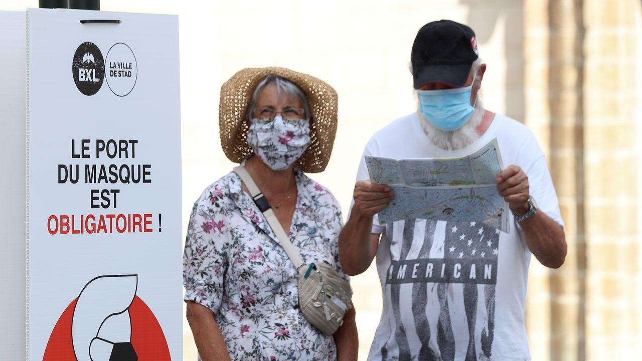 Personas usando mascarillas junto a un aviso que indica la obligatoriedad de las mismas en Bruselas, Bélgica.