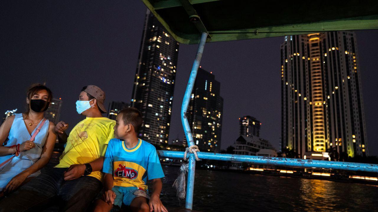 Una familia con mascarillas pasean en un barco desde el que se ve el corazón, en homenaje a los sanitarios, del Hotel Peninsula en  Bangkok, Tailandia