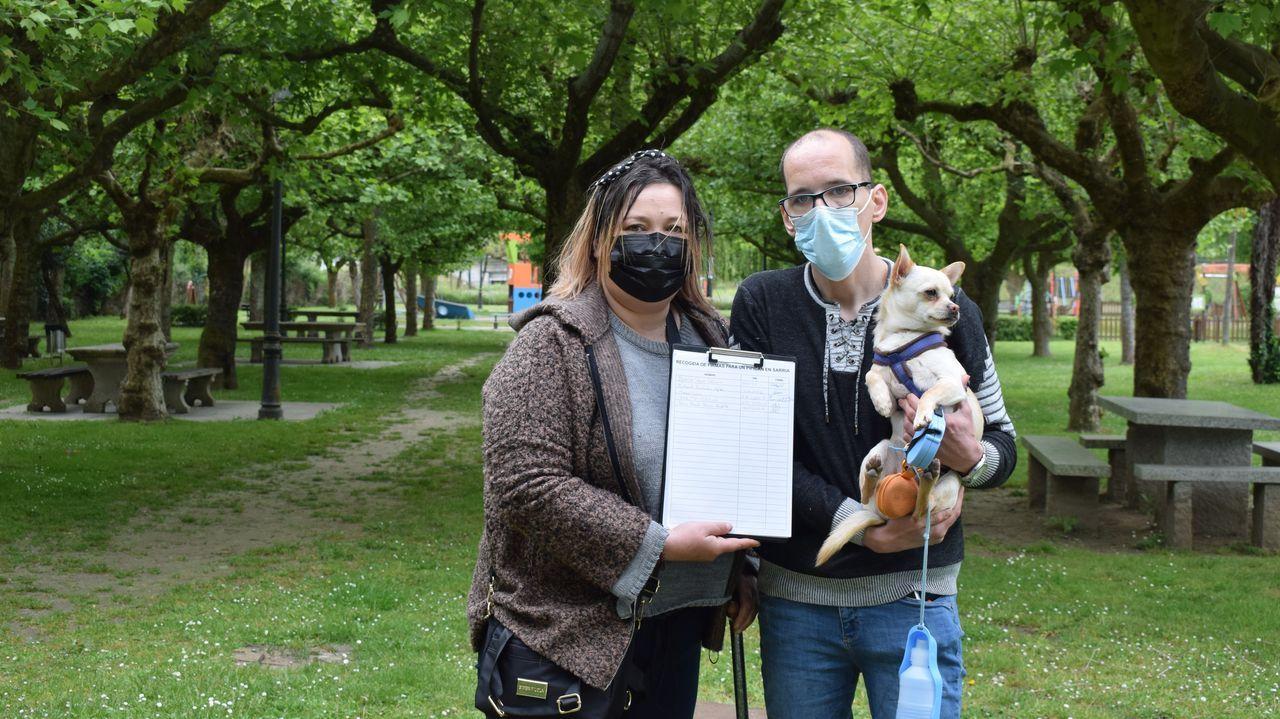 Loida Climent y Óscar Yáñez con el papel de firmas y su perro Keko en O Chanto, donde suelen pasear