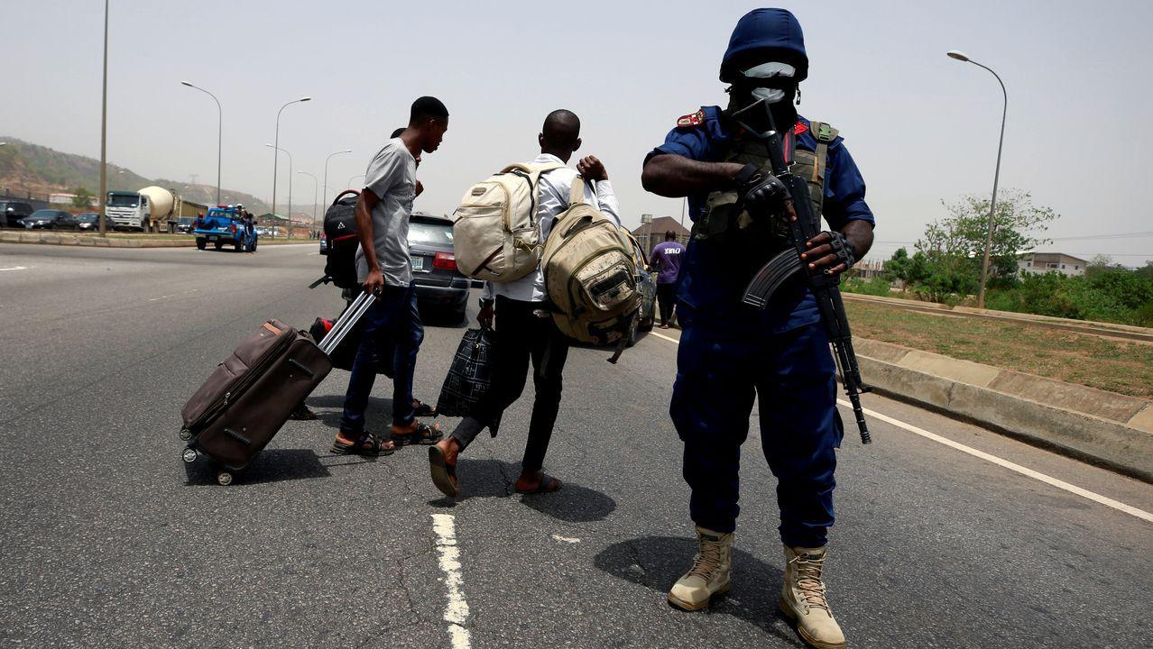 Un guarda de seguridad nigeriano porta máscara de protección mientras trabaja en Abuja