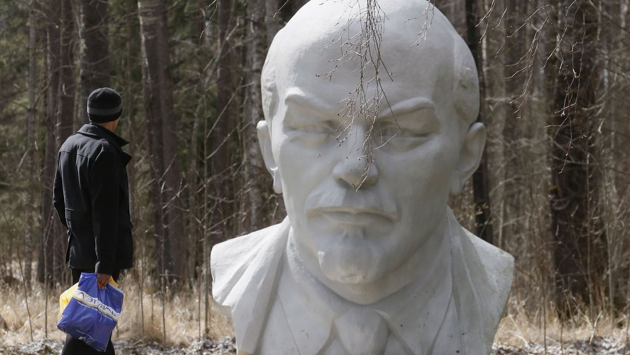Un hombre pasea junto a una escultura de Lenin en San Petesburgo