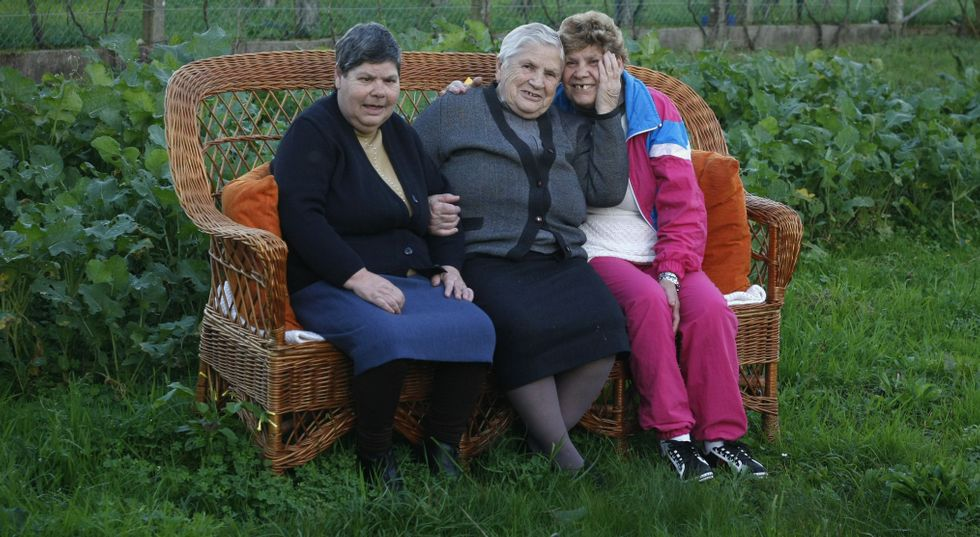 Virginia, con sus hijas María del Carmen y Araceli, en la huerta de la casa que las tres comparten, desde siempre, en Valga.