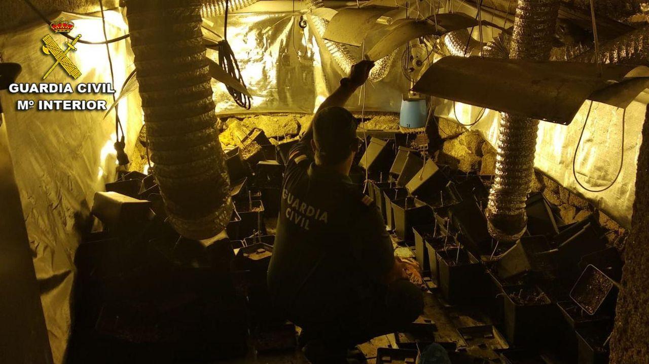 Un agente de la Guardia Civil comprueba los materiales de la plantación de marihuana instalada en la casa de Gondomar.