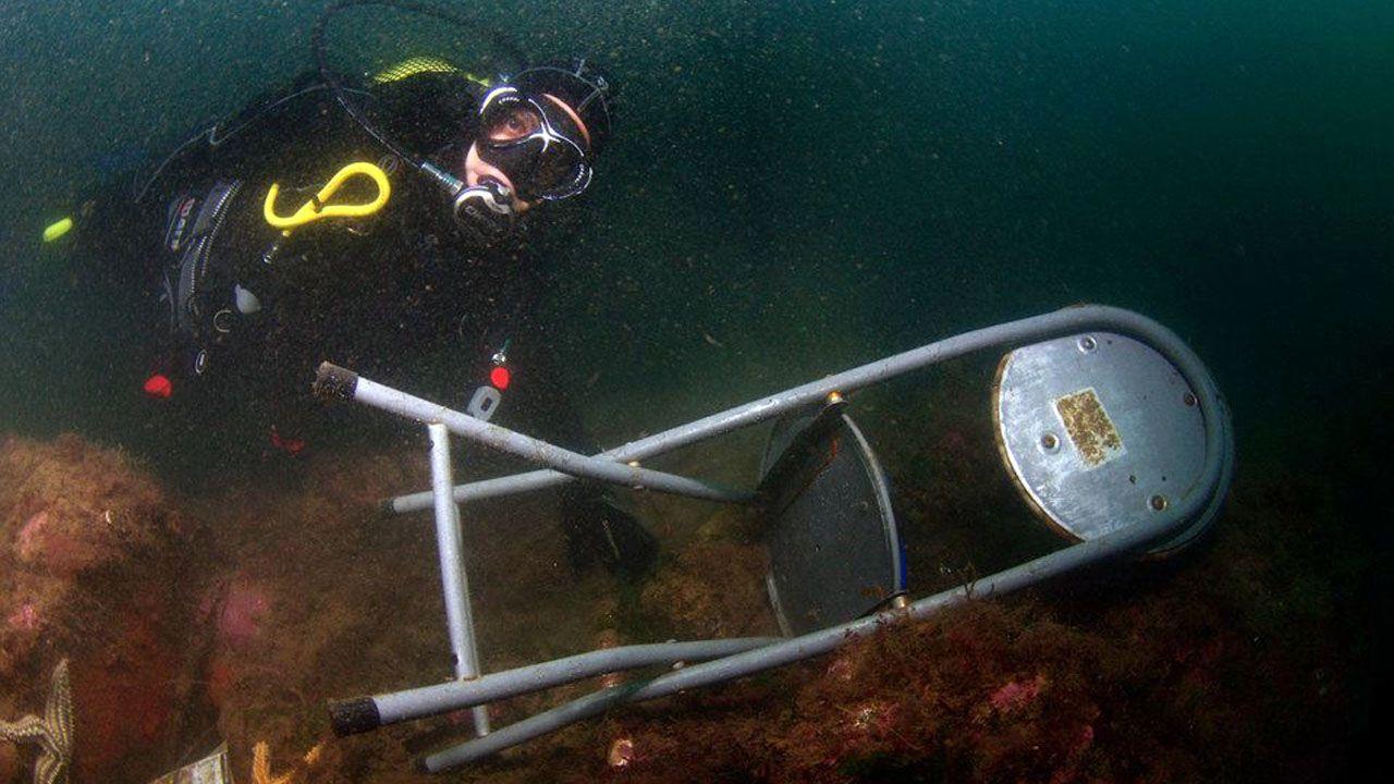 Un buzo saca una silla del fondo del puerto de Cudillero.Participantes en un recorrido por el Camino de Invierno cera de Diomondi, en O Saviñao