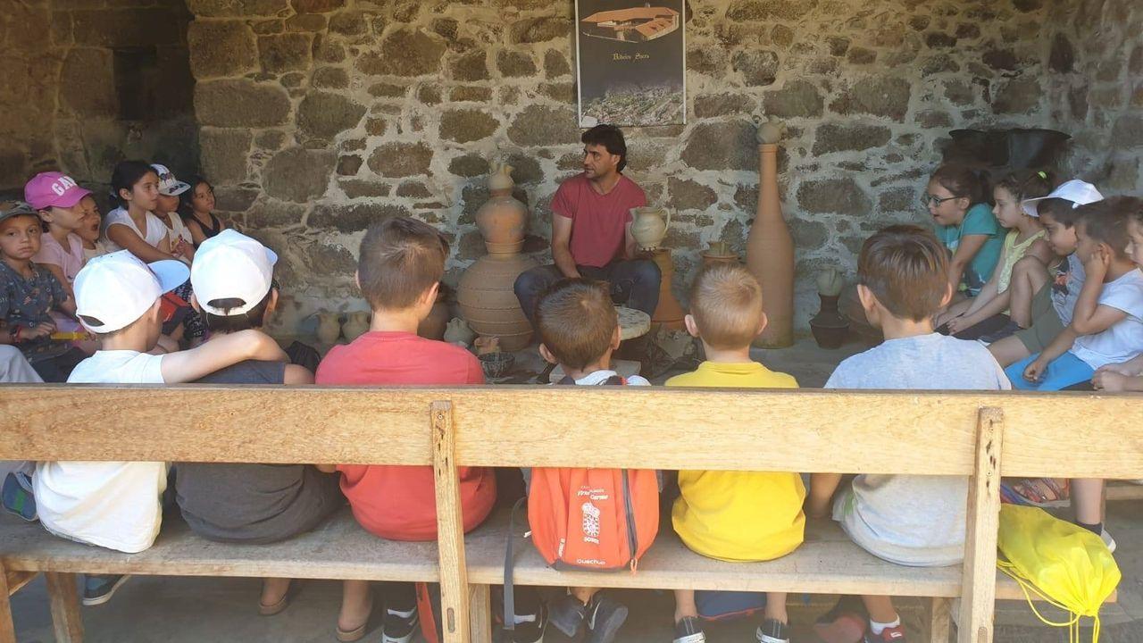 Niños participantes en un campamento de verano de Sober visitan el taller del alfarero Elías González en Gundivós, en una foto de archivo