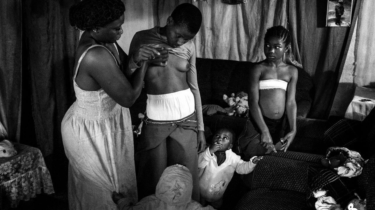 Fotografía cedida por la organización World Press Photo, que muestra la imagen captada por la fotógrafa Heba Khamis, ganadora del 1er premio de la categoría «Contemporary Issues». La foto muestra a Veronica, de 28 años, mientras masaje el pecho de su hija de 10 años Michelle, en compañía de sus otras hijas en Bafoussam, Camerún, el 7 de noviembre del 2016.