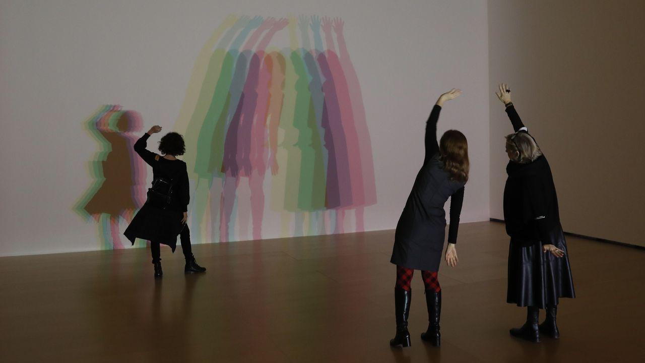 Tres visitantes interactúan con la obra «Tu sombra incierta»