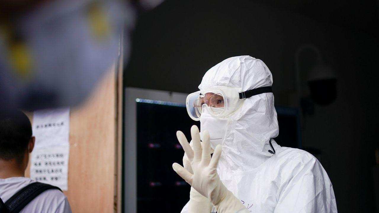 Un sanitario, haciendo pruebas de covid-19 en Wuhan