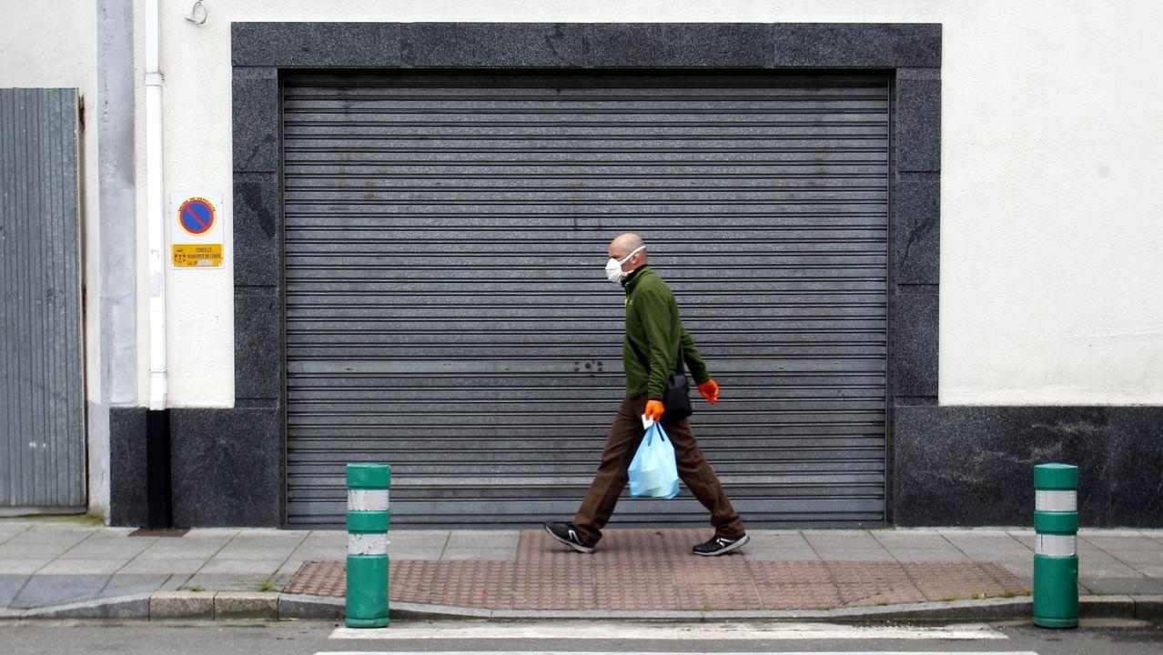 Un hombre camina con una mascarilla por una calle de Monforte