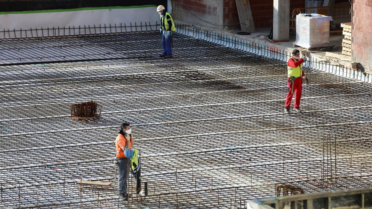 Obreros trabajan en la construcción de un edificio en Cornes (Santiago)