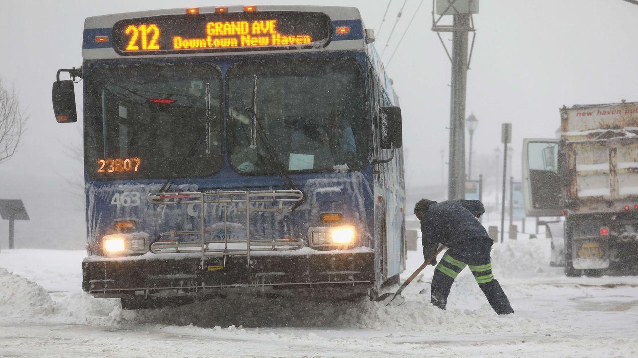 Un trabajador trata de sacar un autobús de la nieve
