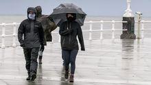 Un grupo de personas pasea por la playa de San Lorenzo de Gijon, bajo la lluvia y el viento