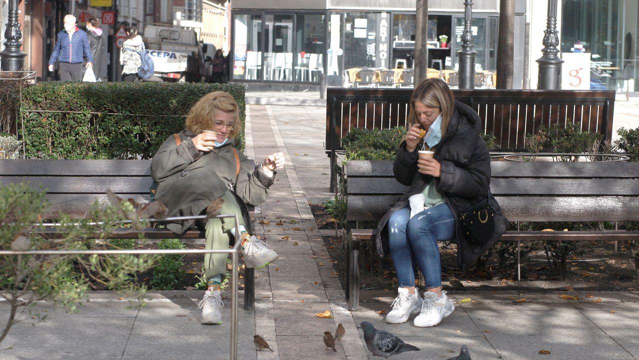 Dos mujeres toman café en una plaza de Gijón