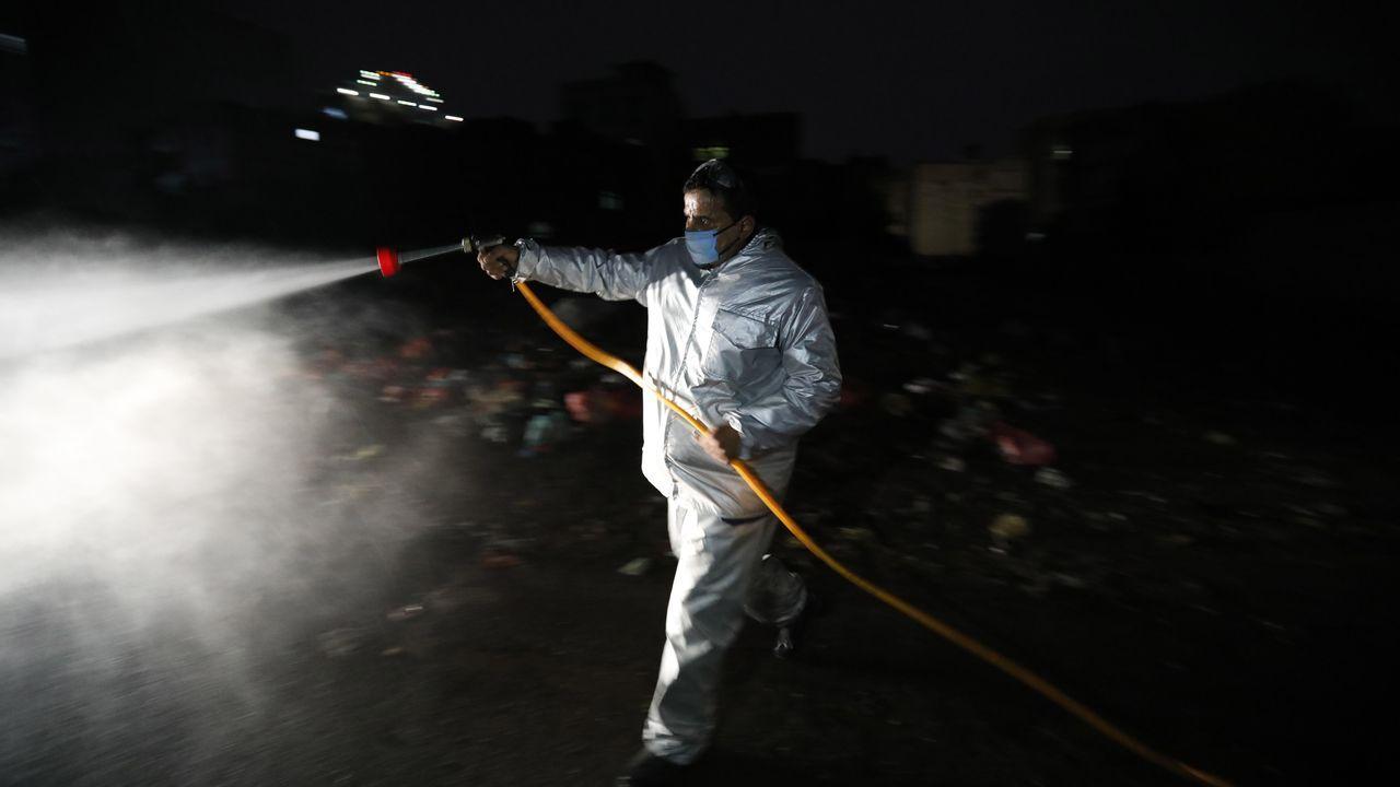 Un voluntario desinfecta una calle en Yemen durante la noche
