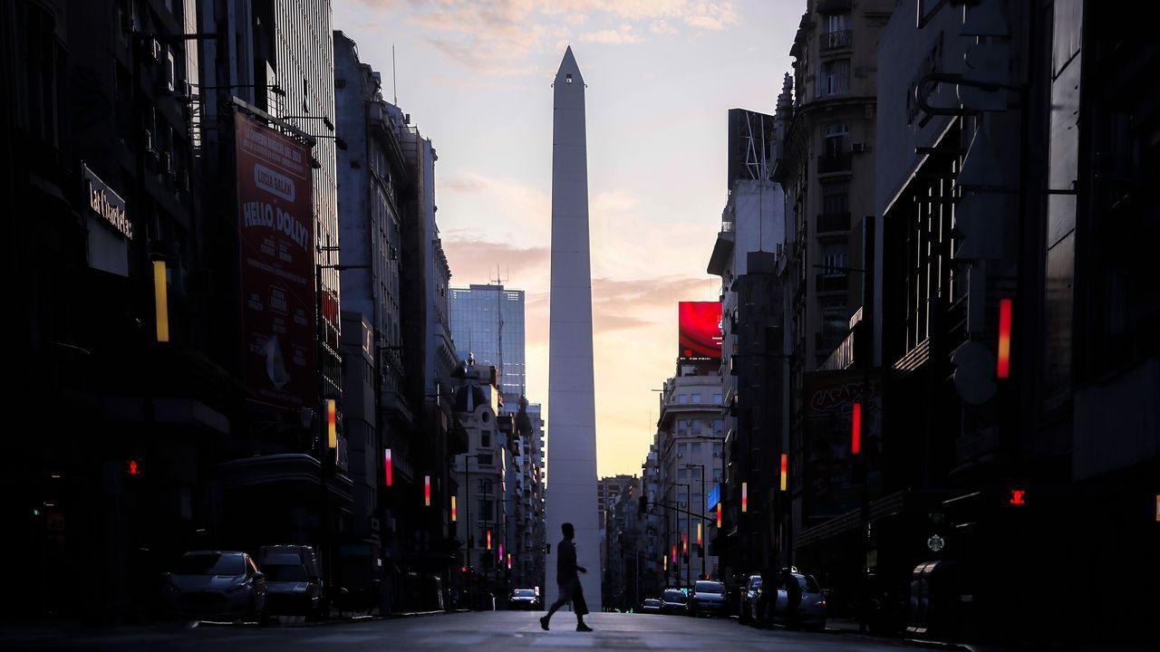 Un transeúnte cruza una avenida vacía en Buenos Aires, bajo confinamiento desde el 20 de marzo