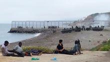 Un grupo de inmigrantes marroquíes observa el despliegue del Ejército de Tierra en uno de los espigones fronterizos de Ceuta