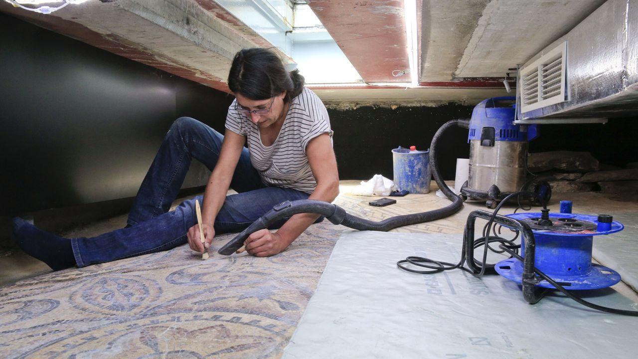La restauradora Iria López limpia los restos de materiales que se sedimentan en los mosaicos romanos de Lugo