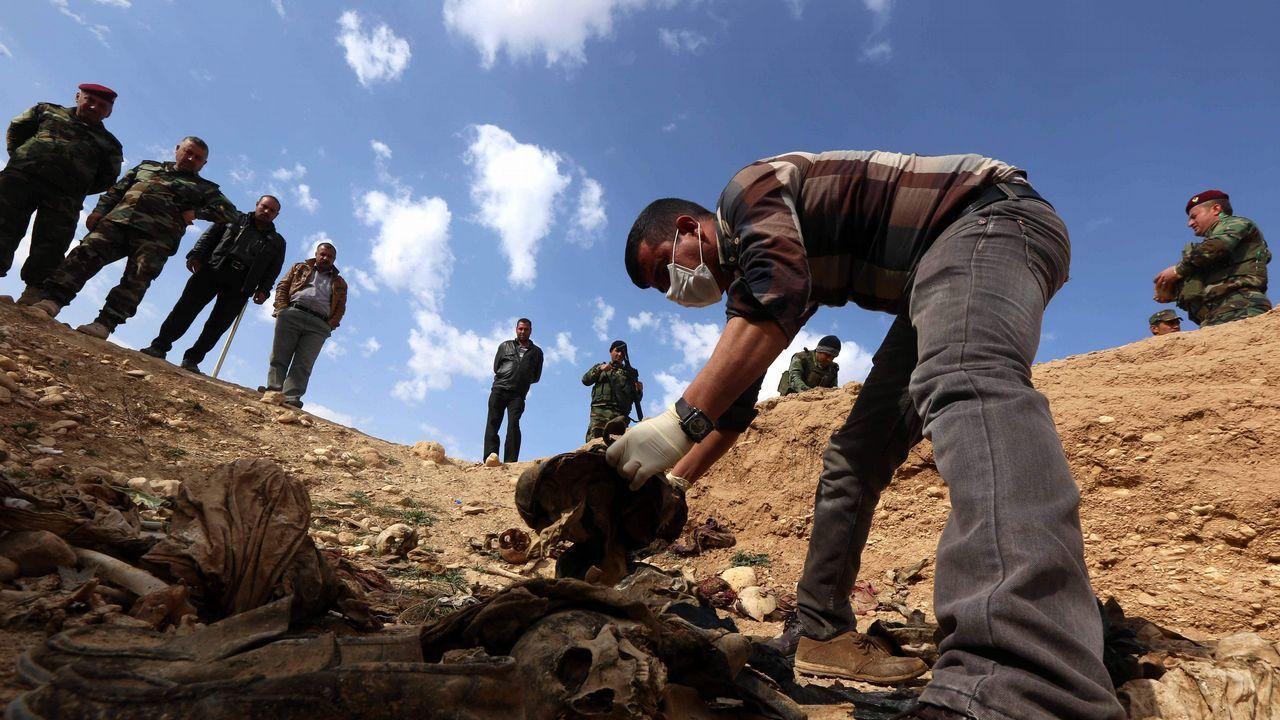 |EFE.Un hombre de la minoría yazidí apila hallazgos en una fosa de la localidad de Sinuni