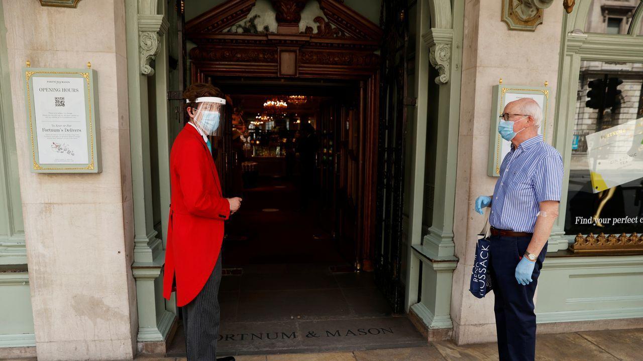 En Londres, un trabajador de los grandes almacenes Fortnum and Mason, con mascarilla y pantalla, da la bienvenida a un cliente