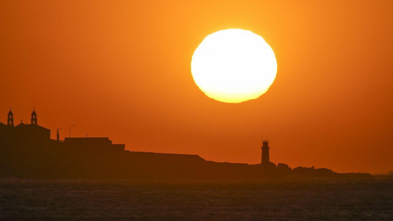 Puesta de sol sobre el santuario de A Barca y el faro de Muxía