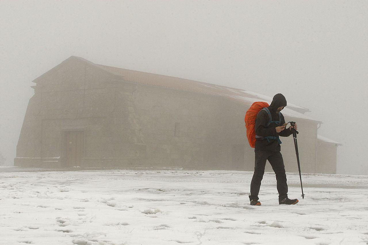 Peregrino en el Camiño de Inverno, al pie de la capilla del Monte Faro en Chantada