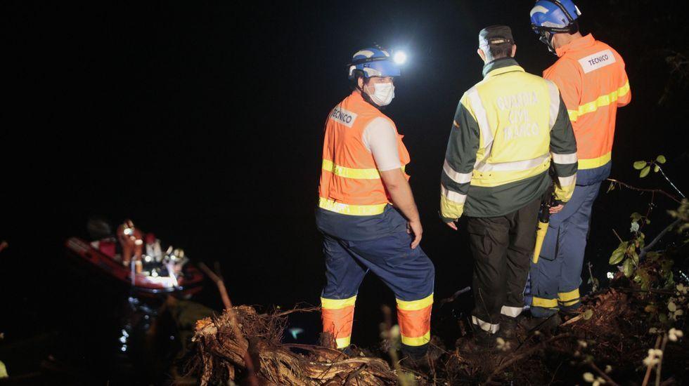 Actividades turísticas para el otoño en la Ribeira Sacra.Dos sanitarios y un guardia civil observan desde la orilla cómo los bomberos rescatan desde una lancha el rescate del cuerpo del camionero