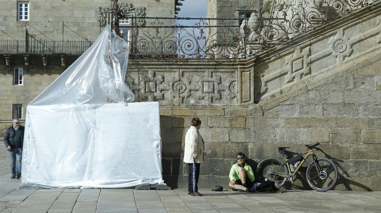 Una lona tapa una de las pintadas realizadas esta semana en la escalinata de la catedral que da al Obradoirro