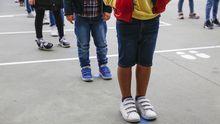 Imagen de archivo de escolares guardando la distancia de seguridad para entrar al colegio