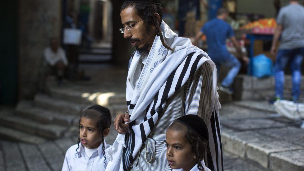 Un judío ultraortodoxo acompañado de sus hijos camina por el barrio musulmán de Jerusalén, donde la mayor parte de las calles permanecen vacías y los comercios cerrados.