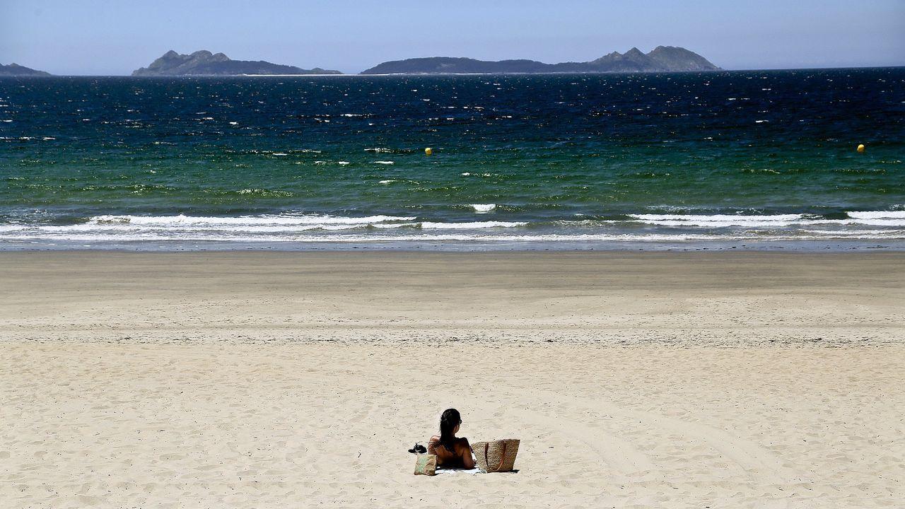 Una mujer disfruta al sol en la playa de Samil, con privilegiadas vistas a las islas Cíes