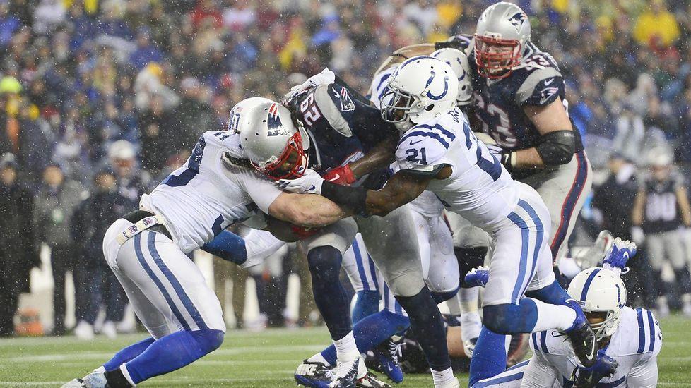 El running back de los New England Patriots LeGarrette Bloun (en el centro) intenta avanzar entre rivales durante un partido.