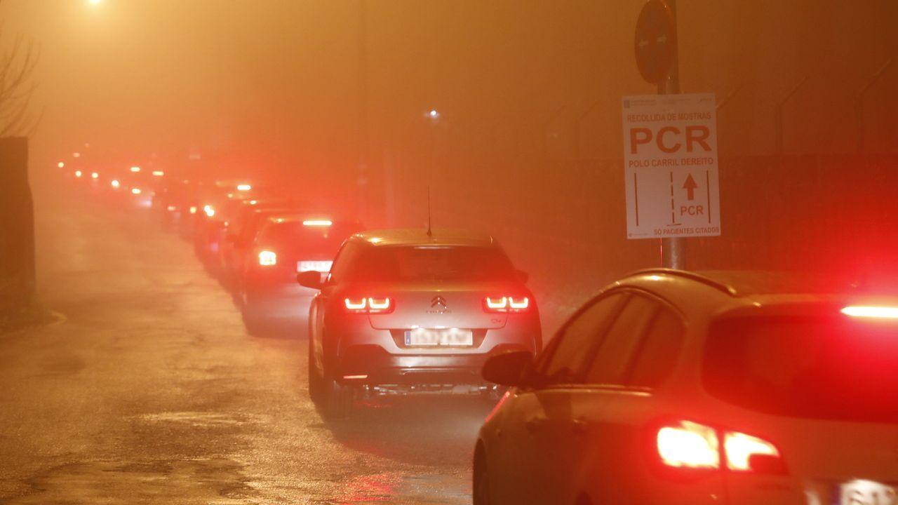 Cola de coches entre la niebla, este lunes por la tarde, para el covidauto del Meixoeiro