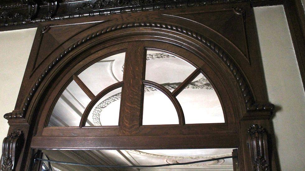 Remate en madera noble tallada sobre una de las puertas de la segunda planta