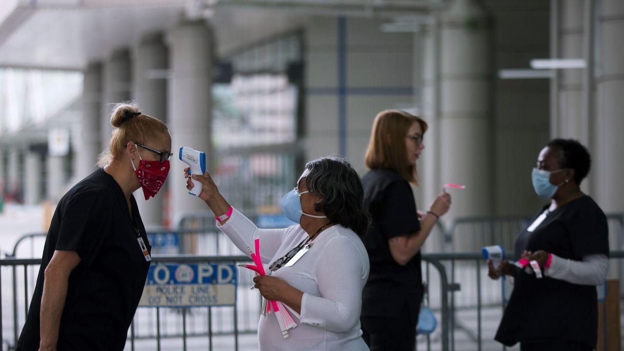Personal médico toma la temperatura durante la preparacion del centro de convenciones Ernest N. Morial para pacientes de coronavirus, en Nueva Orleáns