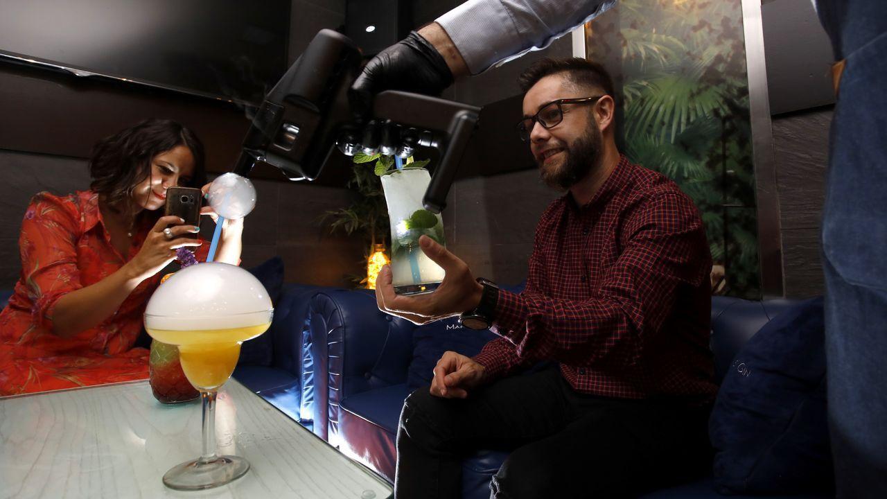 Dos jóvenes fotografían el efecto de una Flavour Blaster sobre su cóctel en el pub Alquimia, en Lugo